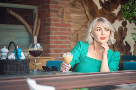 Adult Pensive woman holding a coffee glass looking away in a restaurant terrace