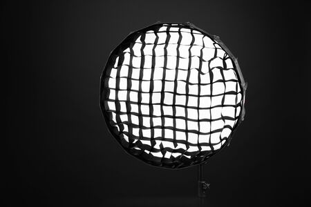 Flash with honeycombs with octagonal soft box on the rack in studio close-up on a black