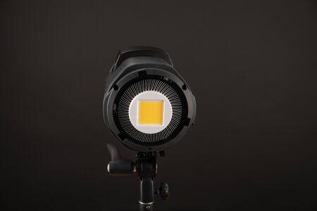 Studio light flash lamp closeup on black Фото со стока