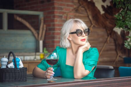 Adult Pensive blonde woman wearing sun glasses holding a glass of red wine looking away in a restaurant terrace Фото со стока