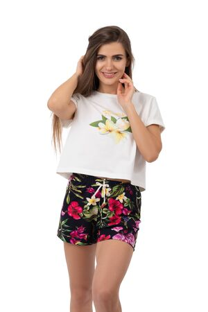 Young pretty woman wearing T-shirt and shorts pajamas isolated on white Фото со стока