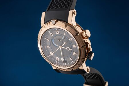 Close up view of nice mans wrist watch on blue
