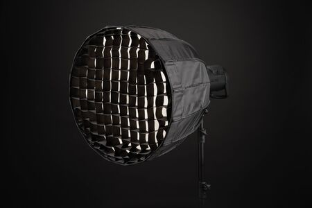 Equipment flash with honeycombs with octagonal softbox on the rack in studio close-up on black