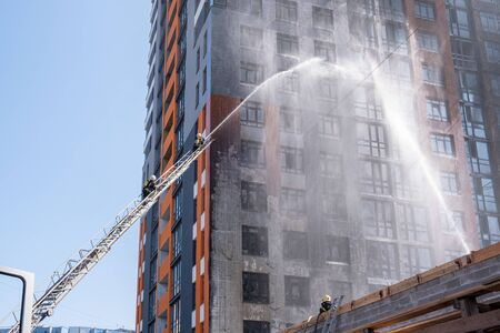 Fireman climbing a ladder with water hose for extinguish fire. Фото со стока