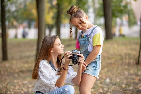 Two girls on the street make a video for the Internet, record a video blog for the camera.