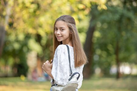 Portrait of Student girl outside in summer park smiling happy.
