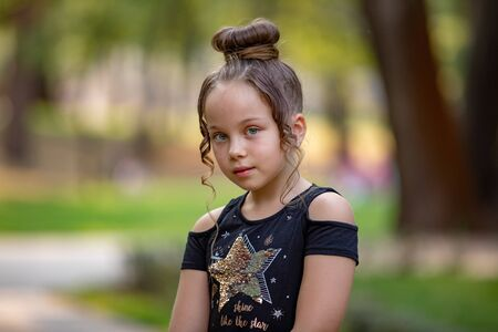 Portrait of Sweet and cute little girl in the park, with sweet, gentle look. Happy childhood concept. 스톡 콘텐츠