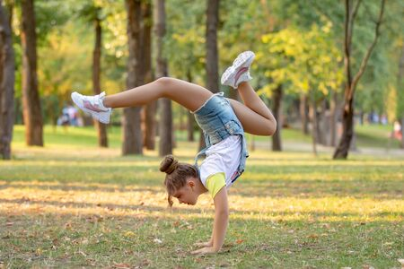 Happy little girl standing on her head on the grass in the park. Childhood concept. Summer holiday. acrobat 스톡 콘텐츠