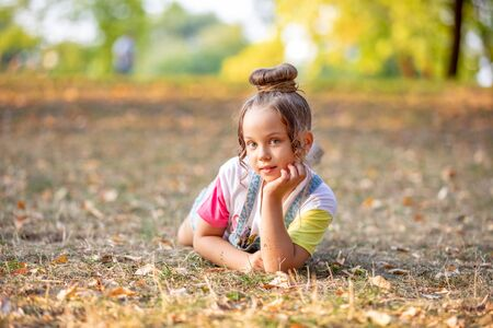 A front portrait of a little girl lying on a colorful leaves in autumn park 스톡 콘텐츠
