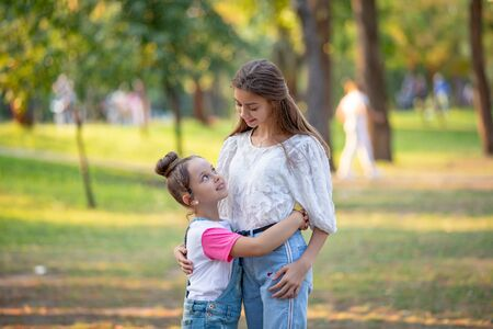 Two sisters hug one another at the park, happy family