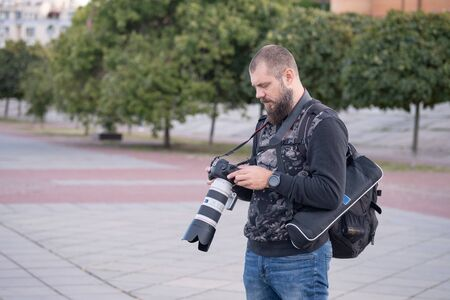 Professional photographer taking a picture outdoor. long lens 스톡 콘텐츠