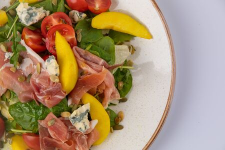 Fresh mix salad with ham, blue cheese, tomato, sunflower seeds and mango on white plate.