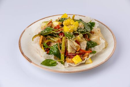 Salad with mango, spinach, bell pepper, sesame seeds lying on white plate. Food flat lay