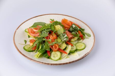 Various fresh mix salad with salmon, tomato, cucumber, onion, bell pepper on white plate, healthy food and diet menu. 스톡 콘텐츠