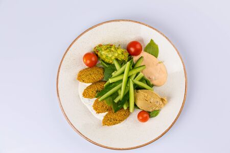 Tasty meat cutlets, avocado, chickpeas, fresh cucumber, hummus on a ceramic plate on white 스톡 콘텐츠