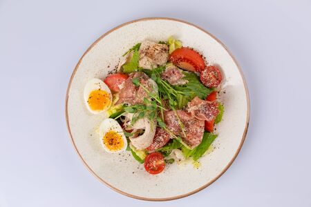 A bowl of fresh lettuce salad with tomatoes eggs prosciutto over white 스톡 콘텐츠