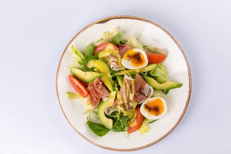 Healthy breakfast. Salad with prosciutto, tomato, egg, avocado and mustard sauce