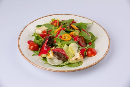 A delicious looking tossed chefs salad or antipasto with meat, Camembert cheese and tomato.