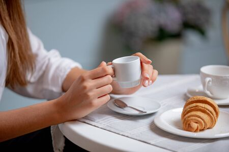 Side view of female hands holding cup of coffee.