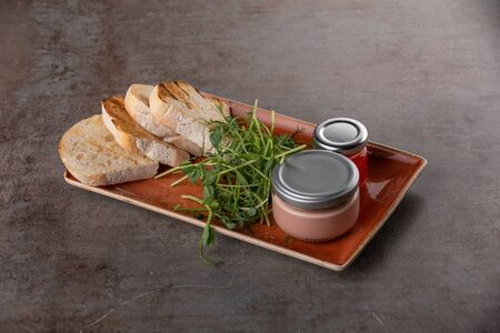 Fresh pate in glass jar with toasted bread on grey table 스톡 콘텐츠