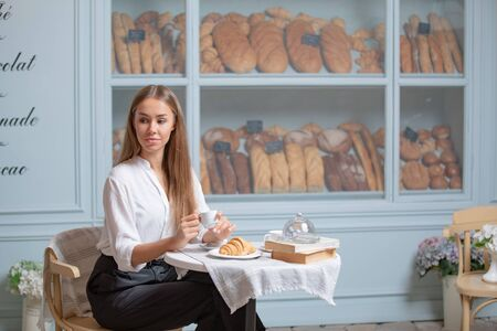 Woman is heaving breakfast with croissant and coffee in the morning.