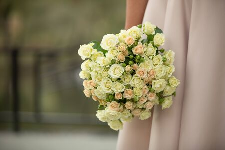the bride holding wedding bouquet of pink and white roses. place for text