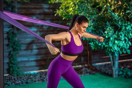 Young woman is training with rubber bands outdoors. Healthy active lifestyle concept. girl doing fitness in the park on the nature.