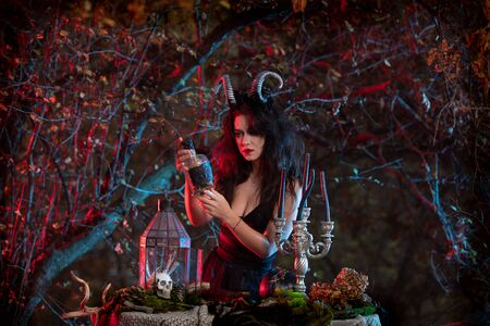 Halloween witch with horns on the head holding a bottle of potion on forest