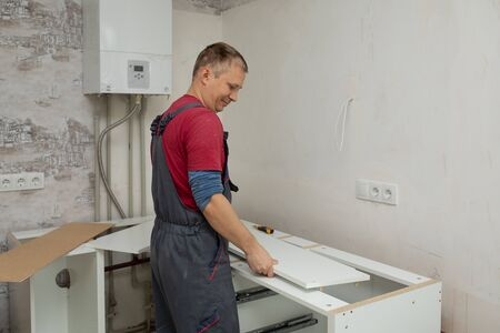 Craftsman kitchen carpenter at kitchen furniture set installation service work. Man during the work