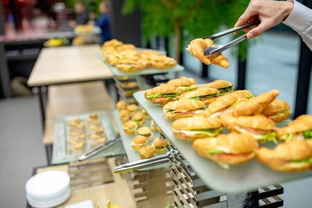 Catering service. Served table with snacks at event. the waiter takes a croissant sandwich with salmon fish on the banquet 写真素材