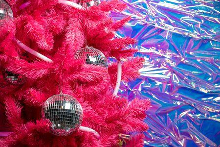 Magic Christmas ball of mirror pieces on an artificial Christmas tree close. Red christmas tree decorated by mirror disco ball.