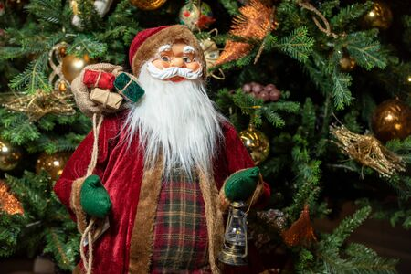 Cute stuffed toy Santa Claus giving a Christmas present. Stuffed toy Santa Claus, a bag of presents on Christmas tree background.