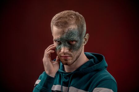 Man with professional horror movie make-up green lizard on dark red