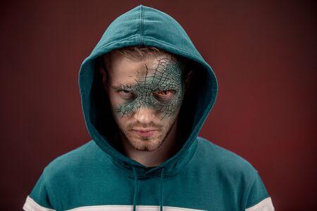 Man with professional horror movie make-up green lizard on dark red Standard-Bild