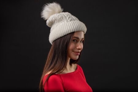 A profile portrait picture of a teenage girl wearing a knitted hat, black background.