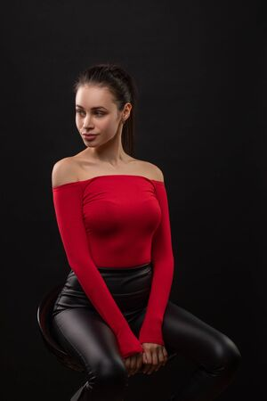 Vertical dramatic portrait with sensual brunette woman in red top with bared shoulders posing sitting on chair on black background. Full height.