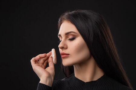 Portrait of young beautiful woman with powder puff. Girl applying makeup on black background Foto de archivo