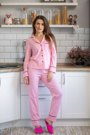 morning young woman in pajama in modern white scandinavian house kitchen, happy and smiling Фото со стока