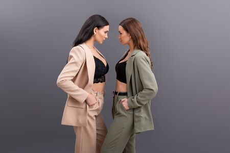 Two attractive business women wearing in suits and tops posing on grey 写真素材