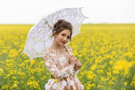 Portrait of young beautiful girl in retro style under a lace umbrella in a field with tall yellow rapeseed flowers.