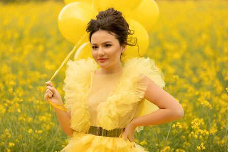 Portrait of romantic brunette teen girl dressing at yellow dress posing with balloons at field with yellow rapeseed flowers with balloons. Happyness and summer time concept