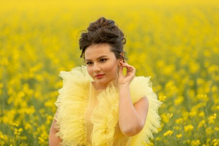Portrait of romantic brunette teen girl wearing at yellow dress posing at field with yellow rapeseed flowers. . Happyness and summer time concept 版權商用圖片
