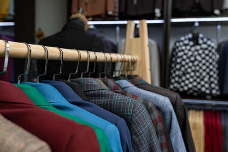 expensive men's clothing store. a row of jackets on hangers. shoping sale background theme. male clothes on hanger in shop