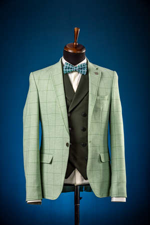 Beautiful mens green jacket suit with vest, shirt and bow tie on a dummy or mannequin on blue