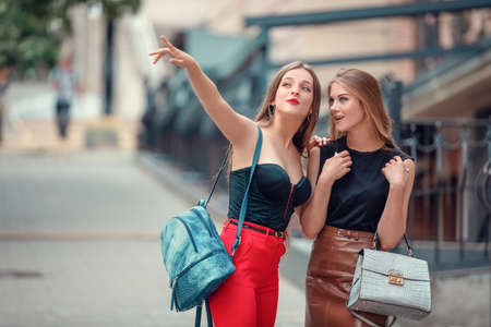 two cheerful modern female tourists while sight seeing in old town. one woman points up to a sight. other excited woman look up, too. two friends women walking around the city