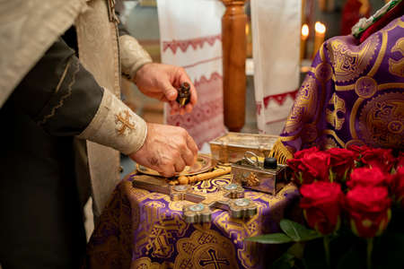 holy oil in the priests hands. the priest prepares for the baptism ceremony of the nebenk in a church