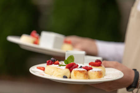 Fresh cheesecakes with berries. Cheesecakes with Strawberry and sour cream on a plates in the waiters hand.