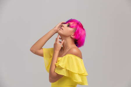 Portrait of a woman with bright colored hair, blue and pink haircut. girl with short hair dressed to yellow dress with open shoulders