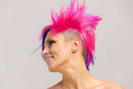 Portrait of a woman with bright colored hair, blue and pink haircut. girl with short hair