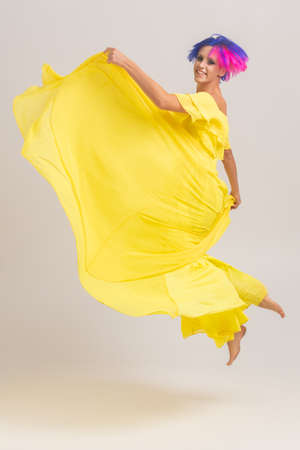 full-length portrait of a woman with bright colored hair, blue and pink haircut. Hair coloring, girl with short hair wearing at long yellow dress with open shoulders jumping on a light cyclorama